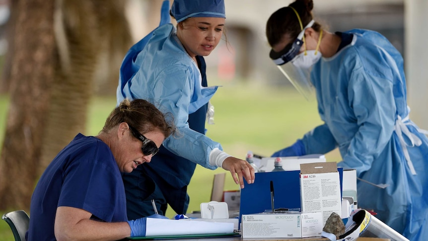 three female healthcare workers in full protective gear at an outside table