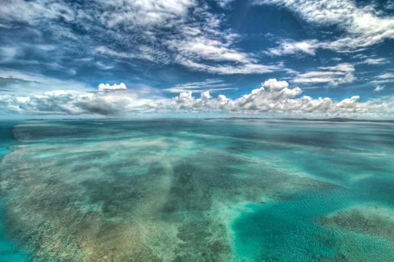 A reef in shallow tropical water with moody clouds overhead.