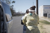 A female health worker helps another tie up her PPE next to a parked van.