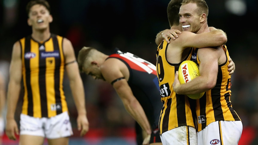 An AFL player holding the ball after the final siren is hugged by a teammate.