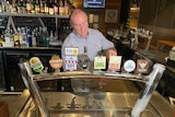 A man pulls a beer behind the bar of the Orion Hotel
