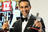 Waleed Aly holds his gold and silver Logies with a Logies sign behind him.