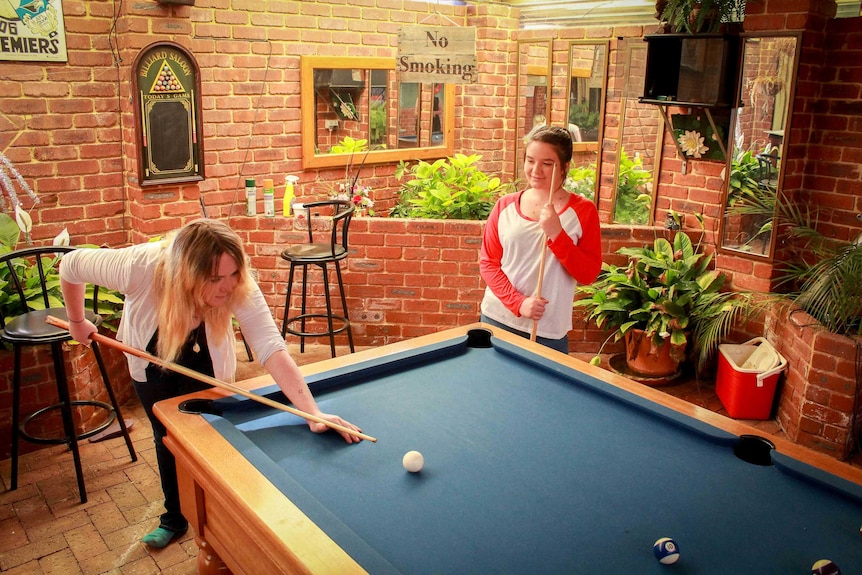 Paige and Tea Johnston playing pool at their grandparents home.