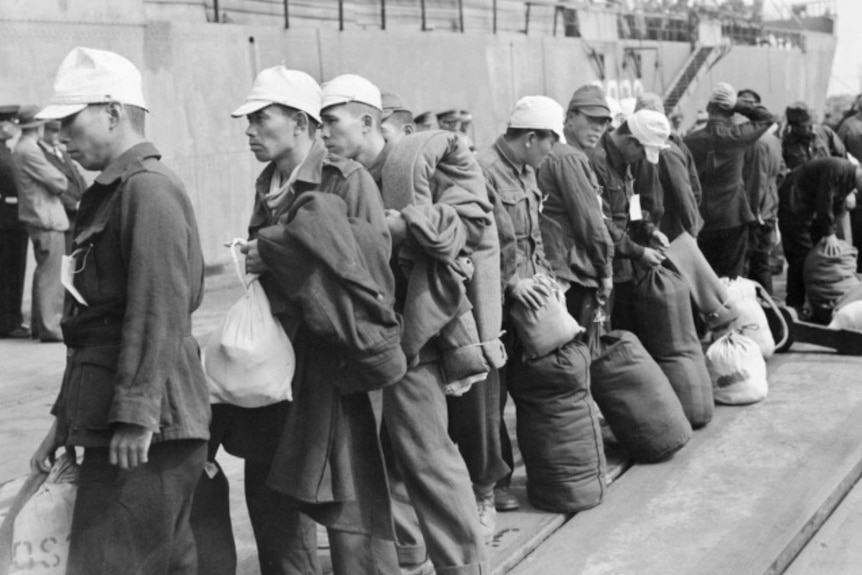 A line of Japanese prisoners of war line up holding luggage preparing to board a ship.