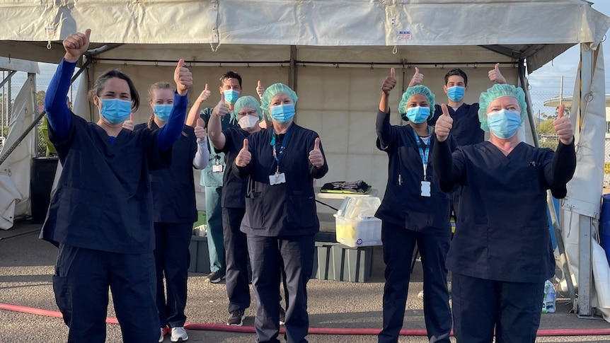 Half a dozen people wearing scrubs and facemasks give the thumbs up to the camera at a COVID-19 testing clinic in Mildura.