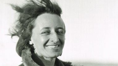 A black-and-white image of a smiling woman dressed in a warm coat standing in outback South Australia.