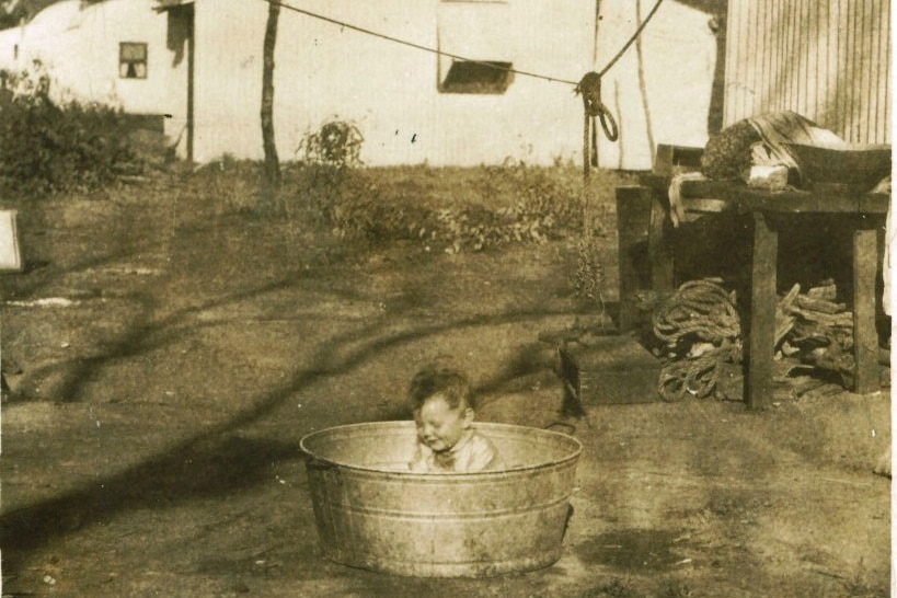 An aged sepia photo shows a small child sitting in a tin tub on the dirt. Behind them is a white tin home.