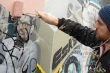 A man in a paint-splattered top uses a roller to paint over a defaced depiction of a bearded, bespectacled man.
