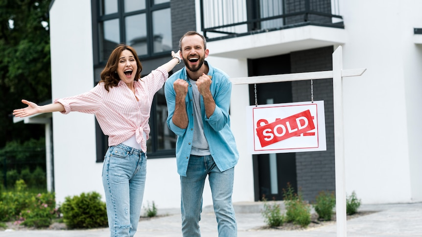 A woman and a man look excited in front of a new townhouse with a 'sold' sign out the front.