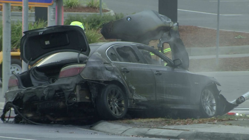 A burnt-out dark BMW car on the side of a road, with smoke coming from the bonnet.