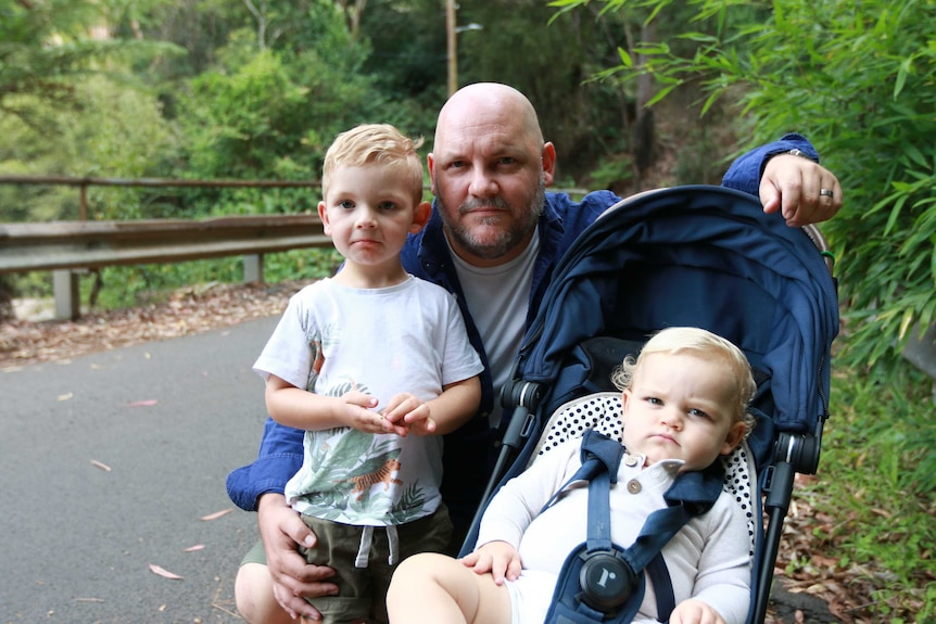 A man and his two children sitting down on a leafy road.