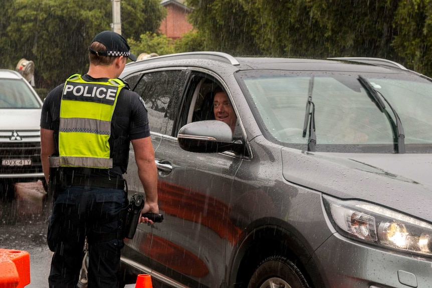 A police officer talking to a driver in a grey 4WD while it's raining heavily.