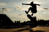 a skateboarder performs a trick in silhouette