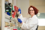 Dr Jemma Evans holds a pipette and test tube in her laboratory.