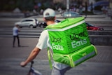 A man on a bike with a green Uber Eats backpack.