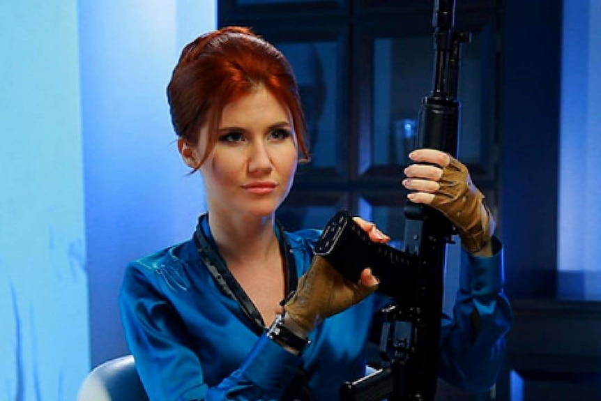 Russian spy Anna Chapman poses with an automatic rifle in a futuristic model shot.