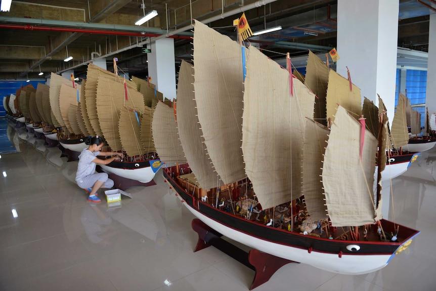 A woman polishes models of the full fleet led by Ming Dynasty eunuch explorer Cheng Ho.