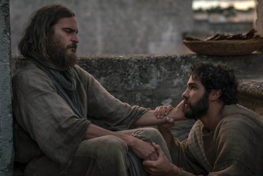 Colour still image from 2018 film Mary Magdalene of Joaquin Phoenix as Jesus Christ clutching the face of Tahar Rahim as Judas.