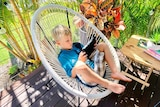 Boy sits on outdoor chair looking at ipad.
