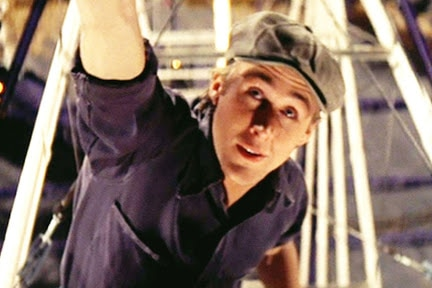 Ryan Gosling in a hat and shirt dangles from a Ferris wheel