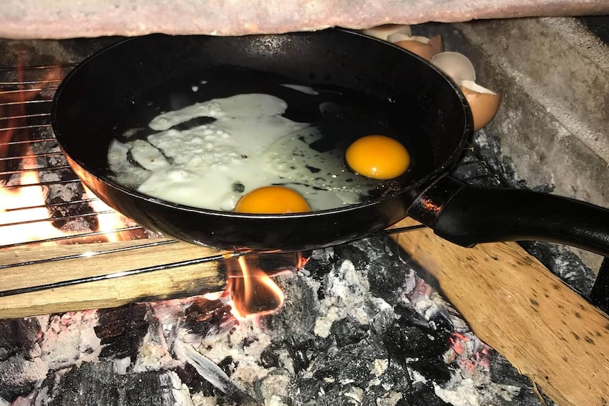 Eggs cook in a pan over a campfire