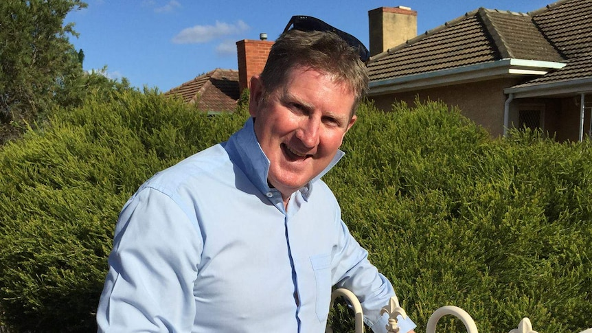 South Australian Liberal MP Terry Stephens drops off election material in a letterbox.