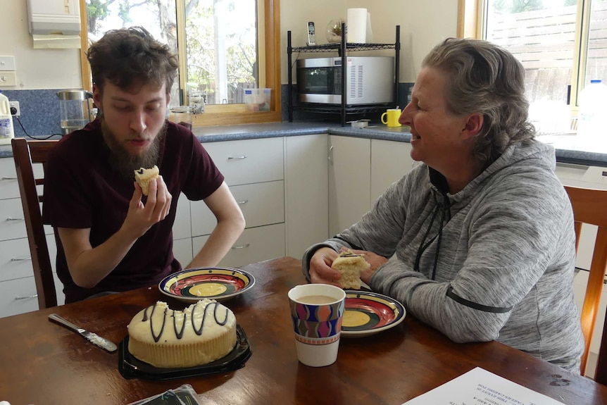 Angela Wilton and her 21-year-old son sitting at a kitchen table eating cake.