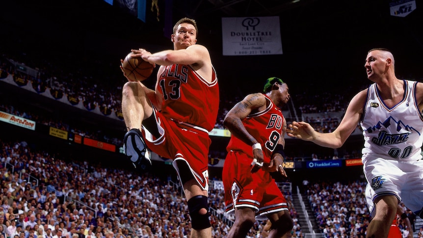 Bulls number 13 Luc Longley lifts his leg in action on the court as a Jazz player approaches