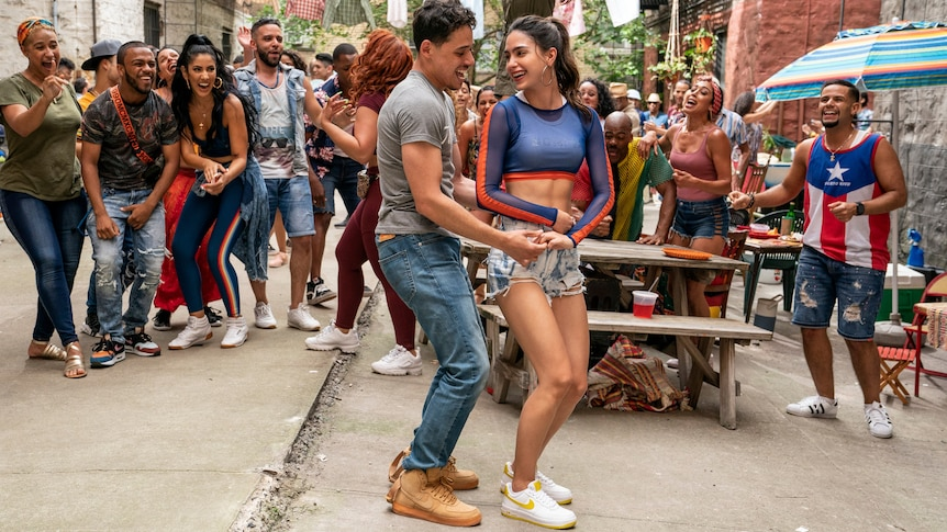 A man and woman dancing in the street surrounded by people.