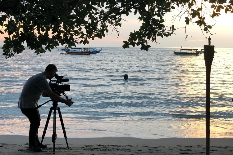 Sunset shot Hemingway standing under a tree filming water.