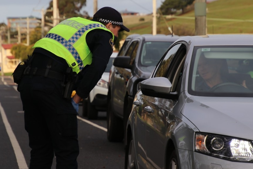 A police officer in Tasmania talks to a driver about their travel