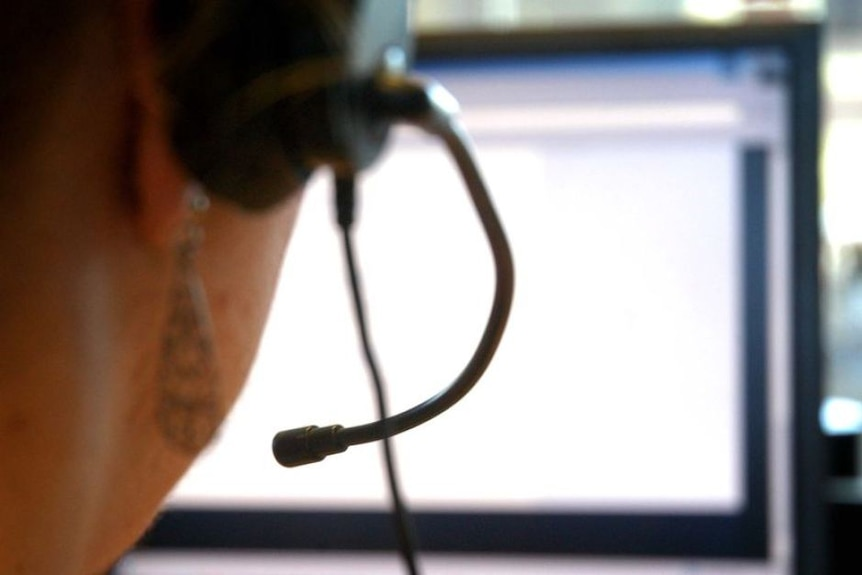 Back of person's head wearing a computer headset and using computer.