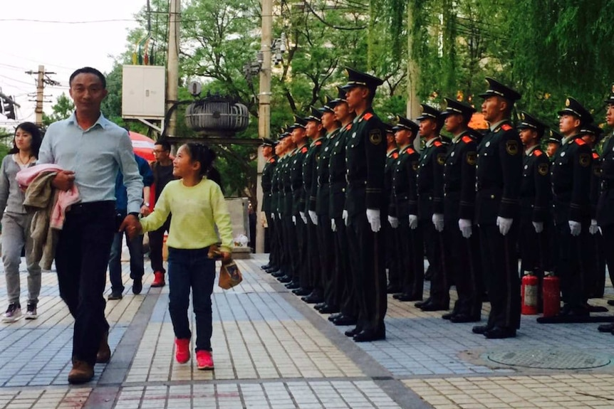Chinese security forces stand in a Beijing street as pedestrians walk by. They are in full uniform with hands at their sides.