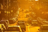 people corssing a busy road during a burning orange sunset