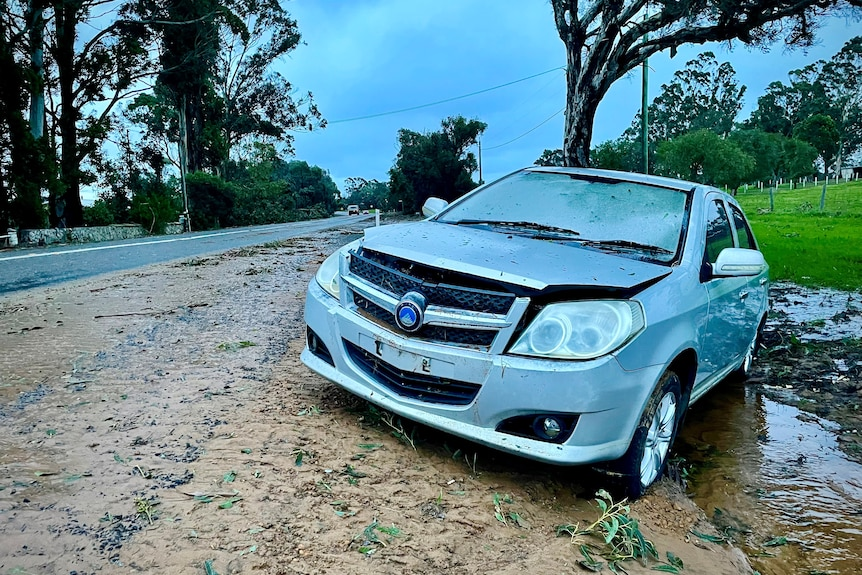 A damaged car sits by the side of a road