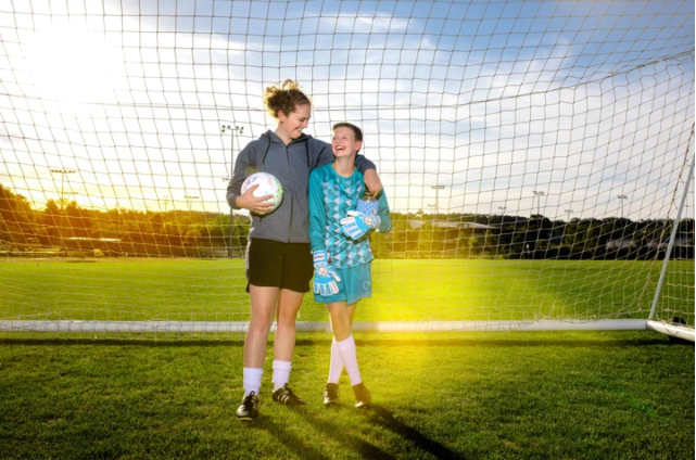 Two female soccer players standing inside the goal net with one wearing her women's specific goalie gloves