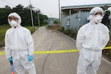 Health workers wear protective suits as a precaution against MERS