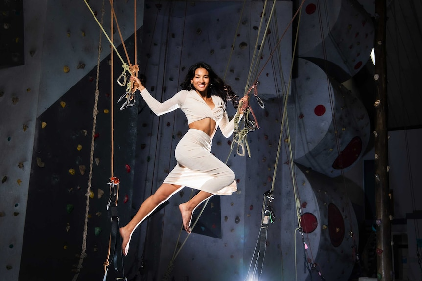 Graduate Veronica McNevin barefoot and smiling while dangling from ropes at indoor rock climbing centre