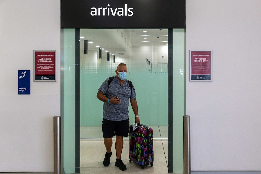 A man wearing a mask and pulling a suitcase walks through the arrivals gate inside the airport terminal.