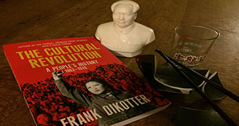 """A book titled """"The Cultural Revolution"""", a mini statue of Mao Zendong, a broken bowl and a glass cup."""