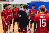A coach and players stand around in a group in a gym at handball training.