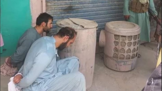 Two detained Afghan officials sitting with their hands tied behind their backs.