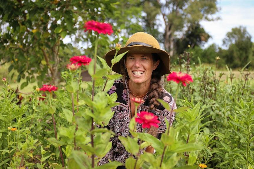 Hannah Lea Robertson smiling behind red flowers