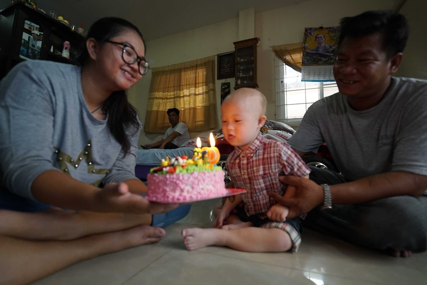 Grammy celebrates his birthday with his family, and gets ready to blow out the candles on his pink coloured cake.