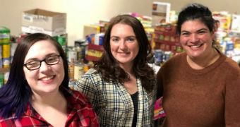 Three women stand with food items stacked in crates and on desks.