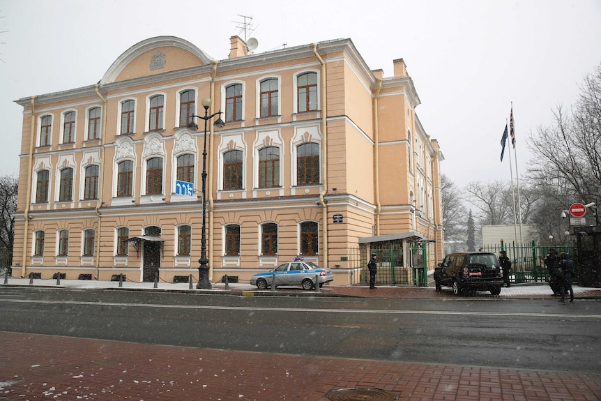Wide shot of a cream-coloured building with guards in front of it.