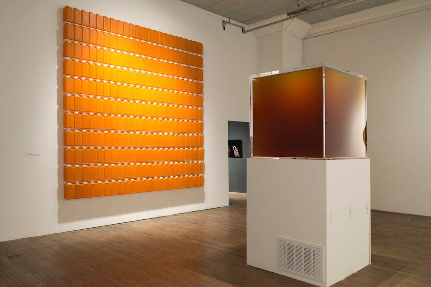 A glass cube of amber liquid next to a wall covered in orange bottles arranged in a square.