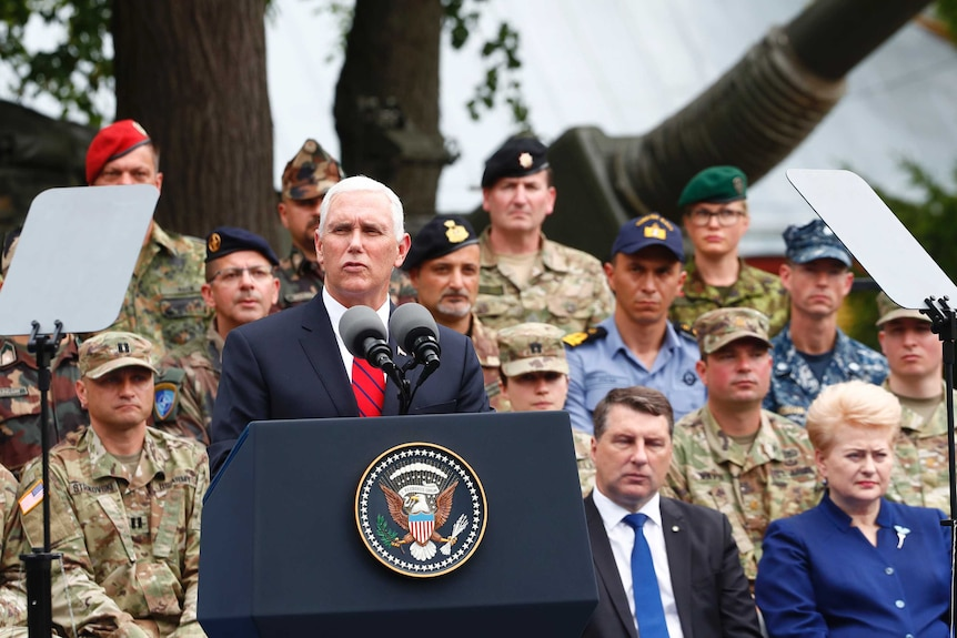 Mike Pence delivers a speech at a lectern with soldiers and others in the background.