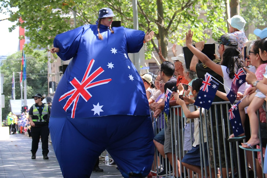 A woman dressed as a giant Australian flag high fives spectators in Melbourne