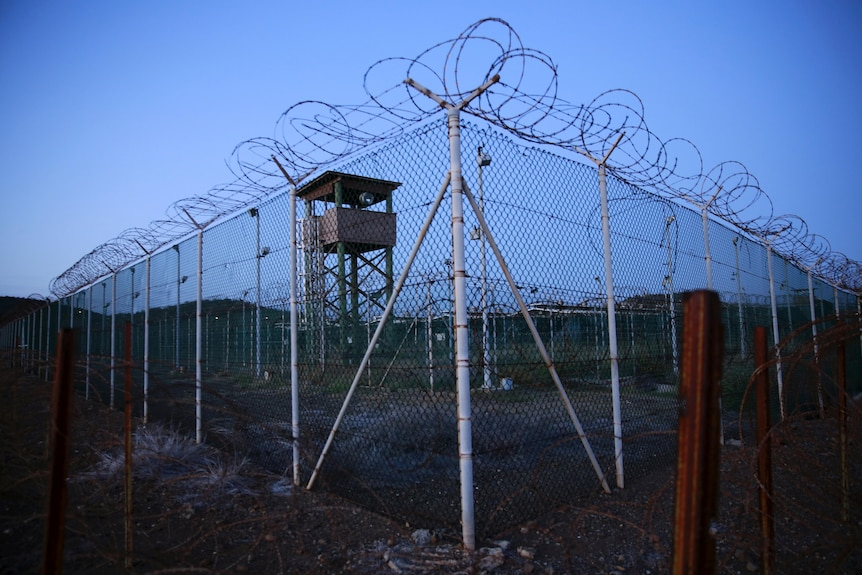 A barbed wire fence and a watch tower before a blue sky at dusk